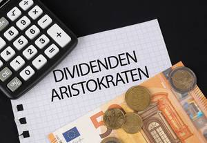 Calculator, money and Dividenden Aristokraten text on black table