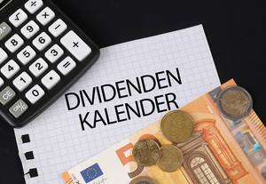 Calculator, money and Dividenden Kalender text on black table
