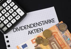 Calculator, money and Dividendenstarke Aktien text on black table