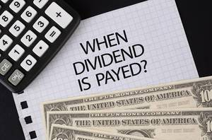 Calculator, money and When Dividend is Payed text on black table