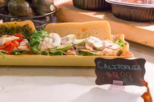 California sandwich: ciabatta, green salad, ham, avocado and sauce