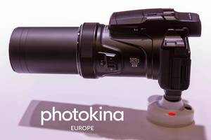 "Camera with 125x optical zoom wide 4k next to picture Titel ""photokina Europe"""