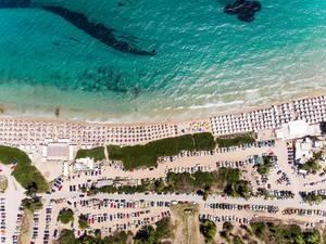 Campingplatz und Strand mit Sonnenschirmen aus der Vogelperspektive