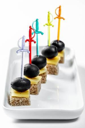 Canape gekleidet auf Schwertern mit schwarzen Oliven und Käse