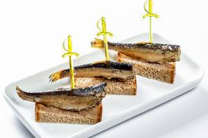 Canape with with smoked sprats and brown bread on plate