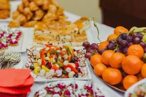 Canapés, gesunder Frühstückstisch mit Obst, Weintrauben, Orangen und Kuchen