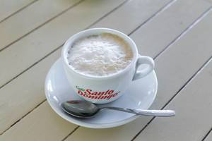 Cappuccino mit Milchschaum in weißer Tasse mit Löffel auf weißem Hintergrund aus Holz