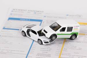 Car insurance report following an accident concept with toy cars on accident statement