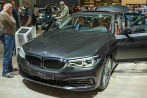 Car show visitors testing the plug-in hybrid vehicle of BMW 5 series 530e xDrive with with all-wheel drive