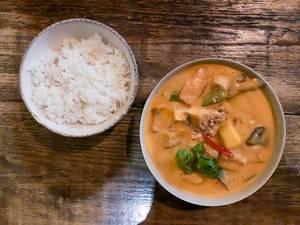 Càri Xoài: scharfes vietnamesisches Gericht mit Bio-Tofu in rotem Kokoscurry mit Mangogeschmack, zusammen mit Süßkartoffeln, Kartoffeln, Shiitake-Pilzen, Zuckererbsen, Cashewkernen, frischer Mango und einer Schüssel Duftreis. Aufnahme von oben