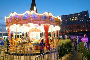 Carousel at Bucharest Christmas Market, The Palace of Parliament on background