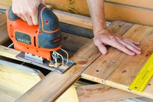 Carpenter using electric jigsaw to cut Wooden Bar