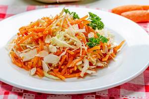 Carrot and cabbage salad on a white plate close-up. Healthy diet (Flip 2019)