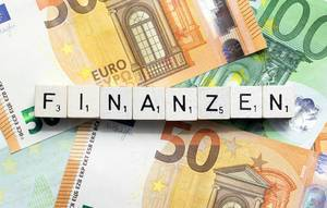 "Cash background with Euro bills and ""Finanzen"" dices"