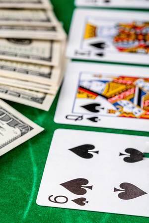 Casino gambling poker cards and money on green desk background