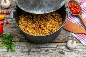 Cast iron cauldron with rice pilaf on the old wooden background (Flip 2019)