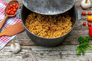 Cast iron cauldron with rice pilaf on the old wooden background
