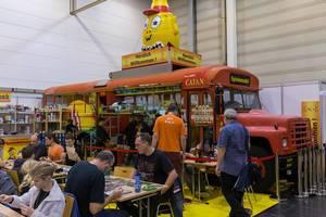 Catan Spielmobil Bus und Fans spielend davor