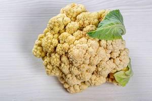 Cauliflower head on white wooden background