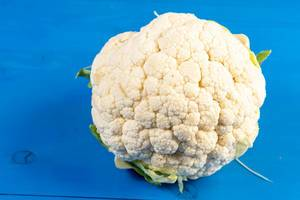 Cauliflower on the blye wooden board