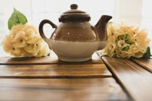 Ceramic brown teapot on a wooden surface (Flip 2019)