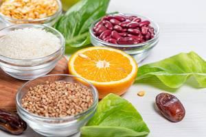 Cerealien-Römersalat, halbe, saftige Orange und einzelne Datteln: Konzeptbild für Zutaten einer gesunden Ernährung
