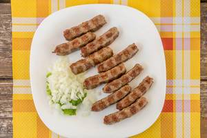 Cevapcici with onion on white plate