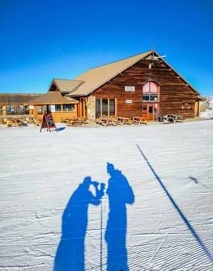 Chalet aus Holz mit Restaurantterrasse im Winter, Personen davor werfen Schatten auf Schnee