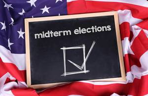 Chalkboard with Midterm elections text on American flag