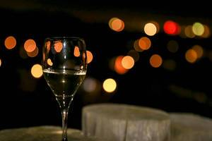 Champagnerglas zu Neujahr mit Bokeh-Lichtern auf dunklem Hintergrund