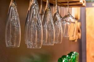 Champagnergläser und Weingläser hängen kopfüber an Holzbrett vor dunkler Wand