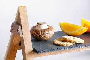 Champignon-Pilz neben Plätzchen und Orangenstücken, auf einer Servierplatte aus Schieferstein