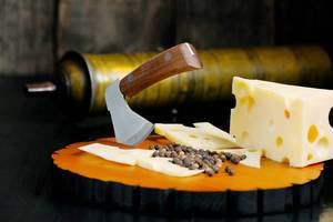 Cheese knife, peppercorns and Swiss cheese