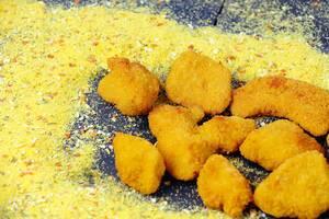 Cheesy chicken bites on background