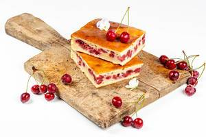 Cherry pie slices on a wooden kitchen Board with fresh cherries