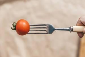 Cherry-Tomate auf einer Gabel aufgespießt, vor braunem Backpapier