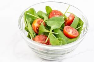Cherry-Tomaten in die Hälfte geschnitten in einer Glasschüssel mit frischem Babyspinat vor weißem Hintergrund