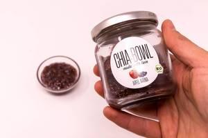 Chia Bowl - Chiapudding mit Apfelaroma in Glas von Hand gehalten und Schale im Hintergrund