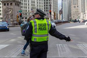 Chicago police officer with a yellow vest at an intersection in Downtown Chicago while a woman crosses the road