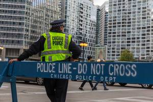 """Chicago Polizist steht neben einem blauen hölzernen Barriere mit Schriftzug """"Police line - Do not cross. Chicago Police Dept"""""""