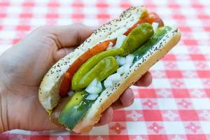 Chicago-style hot dog with yellow mustard, chopped white onions, bright green sweet pickle relish, a dill pickle spear, tomato slices and pickled sport peppers