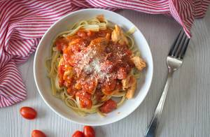 Chicken parmesan with tagliatelle noodles in a bowl with a fork, tomatoes and a kitchen towel aside