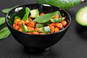 Chickpeas in tomato sauce with avocado slices and spinach