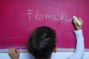 Child writes Flemish word on chalkboard, learning foreign language