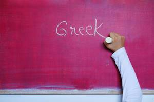 Child writes Greek word on chalkboard, learning foreign language