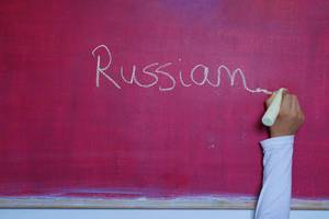 Child writes Russian word on chalkboard, learning foreign language