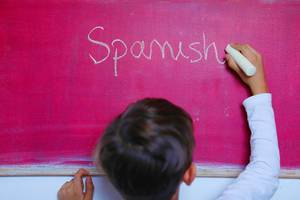 Child writes Spanish word on chalkboard, learning foreign language