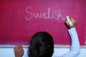 Child writes Swedish word on chalkboard, learning foreign language