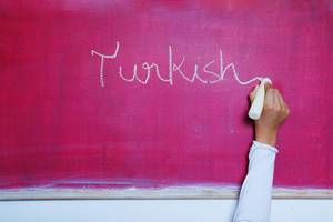Child writes Turkish word on chalkboard, learning foreign language