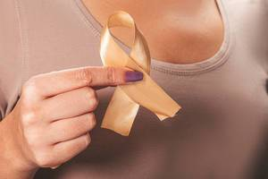 Children Healthcare and World cancer day concept. Gold ribbon in a female hand (Flip 2019)
